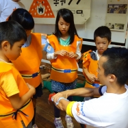 本物の消防士から止血と骨折の応急処置のレクチャーをうける子どもたち