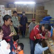 備蓄倉庫にて神戸市産業振興局の方からの説明を聞く参加者